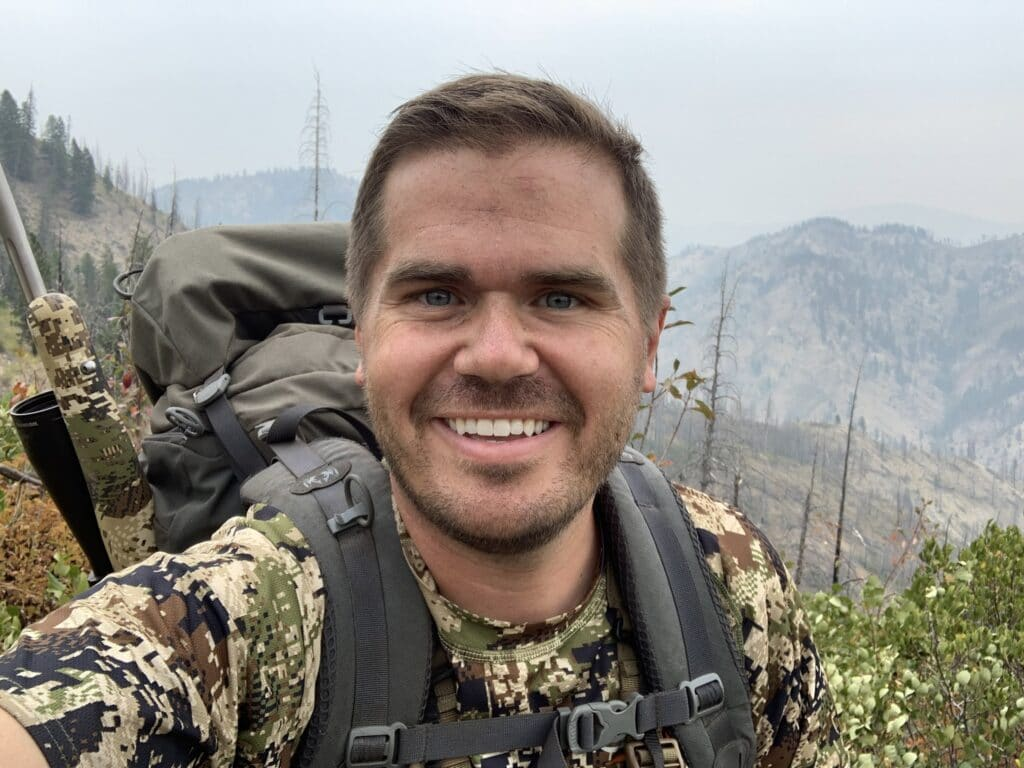 Jim Harmer smiles in the mountains while hunting.